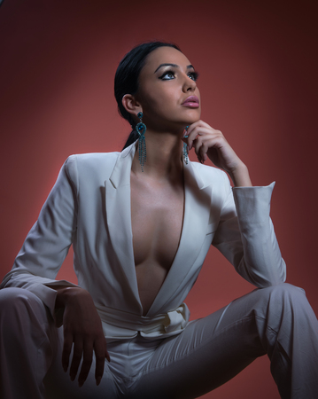 low cut: Young beautiful brunette woman in elegant white suit with trousers sitting. Seductive dark hair girl posing, studio shot. Elegant lady in white suit with jacket with plunging neckline, nostalgia Stock Photo