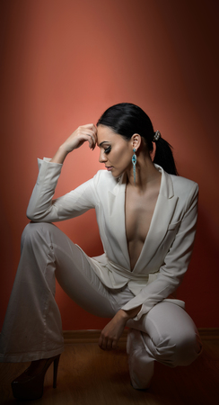 plunging: Young beautiful brunette woman in elegant white suit with trousers sitting. Seductive dark hair girl posing, studio shot. Elegant lady in white suit with jacket with plunging neckline, nostalgia Stock Photo
