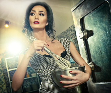 Beautiful brunette mixing ingredients in a bowl. Sensual slim young woman with black bra and low cut neck baking in a professional kitchen. Attractive lady with makeup cooking holding a whisk