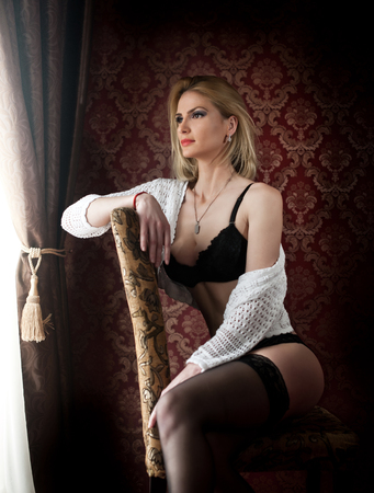long stockings: Attractive and sexy blonde woman with black lingerie and white sweater posing sitting on chair near a window. Sensual female with fair hair and long black stockings looking on the window in daylight Stock Photo