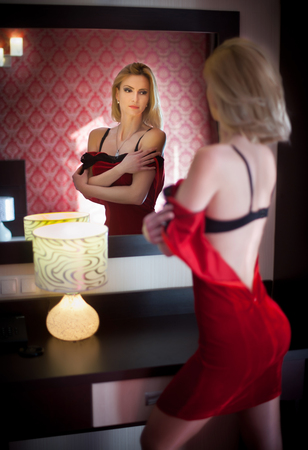 Young beautiful luxurious woman falling the short elegant red dress looking in a large mirror. Back side view of sensual blonde in red on high heels. Seductive woman undressing in modern scenery