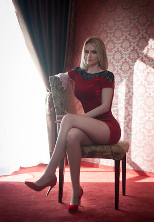Attractive and sexy blonde woman with red short tight fit dress posing sitting on chair near a window. Sensual female with fair hair and red high heels shoes daydreaming daylight. Long legs female