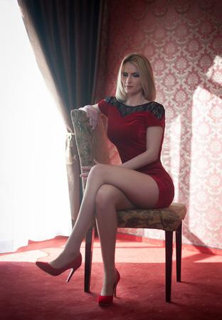 modelos posando: La mujer rubia atractiva y atractiva con rojo corta apretada posando vestido cabe sentado en la silla cerca de una ventana. Hembra sensual con el pelo rubio y los altos zapatos rojos de tacón soñando despierto luz del día. Piernas largas femeninas