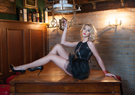 Attractive and blonde woman with short black lace dress posing provocatively lying on wooden table in vintage kitchen. Beautiful woman with curly fair hair and high heels shoes in vintage room