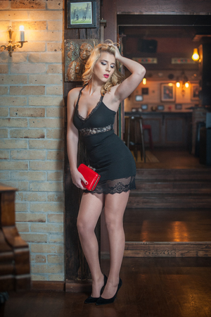 Young beautiful blonde woman in short black lace dress posing provocatively near bricks wall, vintage scenery. Elegant romantic voluptuous lady holding a red clutch standing indoors, retro style Stock Photo