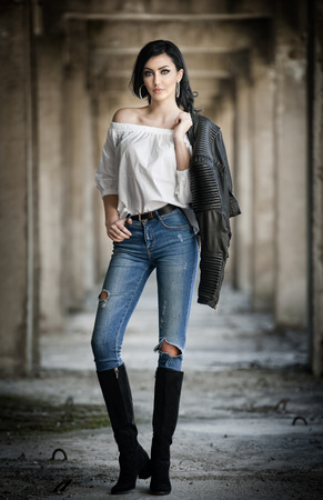 Portrait of beautiful sexy young woman with modern outfit, leather jacket, jeans, white blouse and black boots, in urban background. Attractive young brunette with long hair and blue eyes posing. Standard-Bild