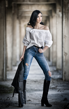 Portrait of beautiful sexy young woman with modern outfit, leather jacket, jeans, white blouse and black boots, in urban background. Attractive young brunette with long hair and blue eyes posing. Stock Photo