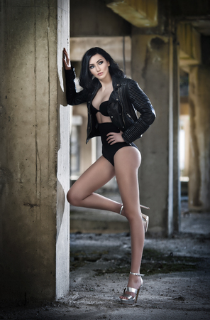 Portrait of beautiful sexy young woman with black outfit, leather jacket over lingerie, in urban background. Attractive brunette with perfect long legs on high heels silver sandals posing fashion.
