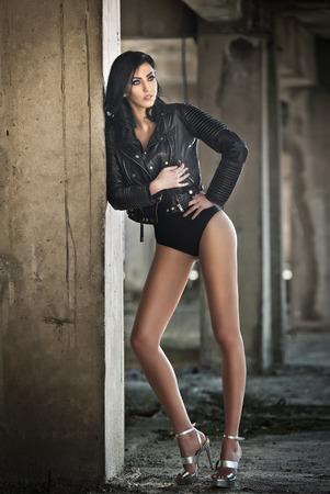 sandalias: Retrato de mujer joven y atractiva con el equipo negro, chaqueta de cuero sobre la ropa interior, en el fondo urbano. atractiva morena de piernas largas perfectas en tacones altos sandalias de plata de manera que presenta.