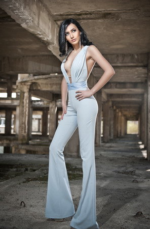 decolletage: Portrait of beautiful sexy young woman with elegant overall, in urban background. Attractive young brunette with long hair and blue eyes posing fashion in white outfit. Long legs woman, side view Stock Photo