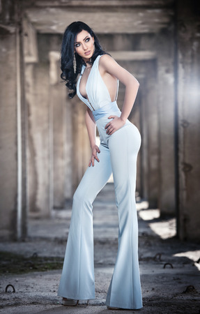 Portrait of beautiful sexy young woman with elegant overall, in urban background. Attractive young brunette with long hair and blue eyes posing fashion in white outfit. Long legs woman, side view Stock Photo