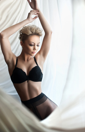Attractive fair hair model with black pantyhose and bra posing provocatively wrapped in white curtains. Portrait of sensual short hair blonde in daylight. Beautiful female in window posing alone.