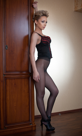 tights: Charming young blonde woman in black corset and tights leaning against wooden wardrobe. Sexy gorgeous short hair girl near vintage wardrobe. Full length portrait of sensual female posing provocatively Stock Photo
