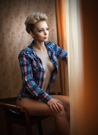Attractive sexy blonde with blue checkered shirt looking on the window in daylight. Portrait of sensual short fair hair woman wearing an open blouse indoor scene. Beautiful long hair woman daydreaming Stock Photo
