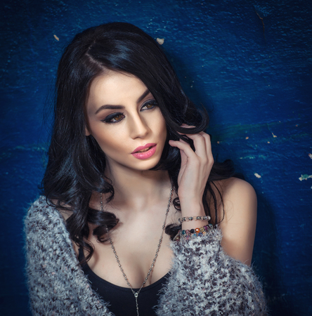 low cut: Beautiful girl with makeup posing, old wall with peeling blue paint on background. Pretty brunette with fluffy sweater over low cut black top. Attractive dark hair young woman with gorgeous eyes Stock Photo