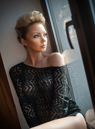 see through: Attractive sexy blonde with black see through blouse looking on the window in daylight. Portrait of sensual short fair hair woman wearing low shoulder top, indoor scene. Beautiful woman daydreaming