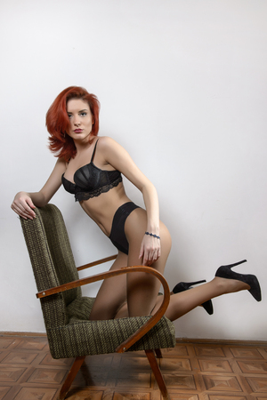 Attractive red hair model with black lingerie sitting provocatively on chair, gray background.  sensual woman with long legs and high heels. Beautiful redhead female in black posing provocatively.