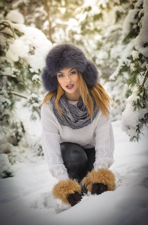 Attractive woman with brown fur cap and jacket enjoying the winter. Side view of fashionable blonde girl posing against snow covered bridge. Beautiful young female with cold weather outfit Stockfoto