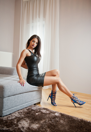 Beautiful brunette young woman wearing black leather short dress sitting on bed. Fashionable female with attractive body posing provocatively, indoor. Sensual girl on blue sandals with high heels