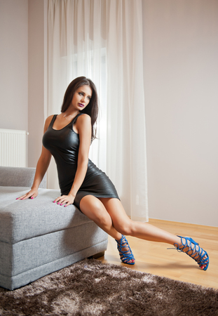 Beautiful sexy brunette young woman wearing black leather short dress sitting on bed. Fashionable female with attractive body posing provocatively, indoor. Sensual girl on blue sandals with high heels 스톡 콘텐츠