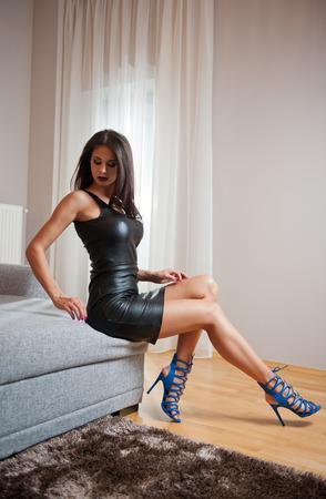 Hermosa joven morena con vestido corto de cuero negro sentada en la cama. Mujer de moda con cuerpo atractivo posando provocativamente, interior. Chica sensual en sandalias azules con tacones altos