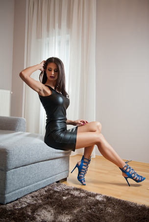 Beautiful sexy brunette young woman wearing black leather short dress sitting on bed. Fashionable female with attractive body posing provocatively, indoor. Sensual girl on blue sandals with high heels Фото со стока