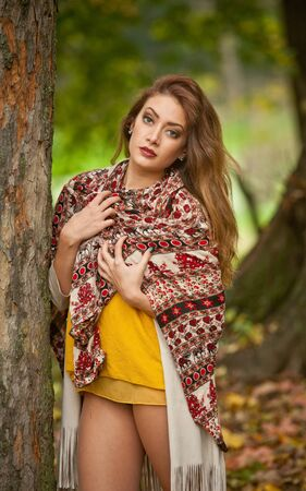 Happy Portrait fashion of a beautiful young Caucasian woman with a scarf,long legs  and yellow pullover in autumn park,red green yellow threes. Autumn, season and people concept.Autumn lifestyle
