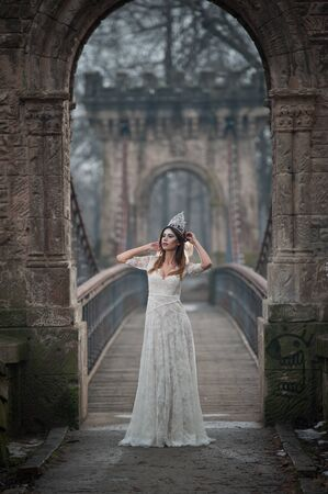 Lovely young lady wearing elegant white dress enjoying the beams of celestial light and snowflakes falling on her face. Pretty brunette girl in long wedding dress posing on a bridge in winter scenery Standard-Bild