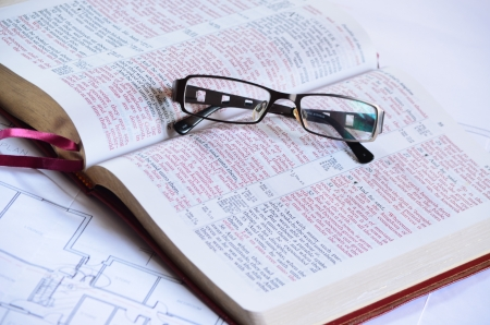 Bible, blueprints and glasses photo