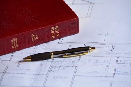 Holy bible, blueprints and pen photo