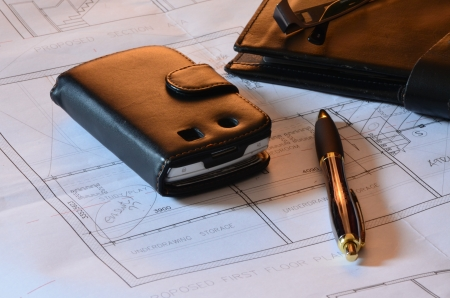 redemption of the world: Architects blueprints, Mobile phone and pen Stock Photo