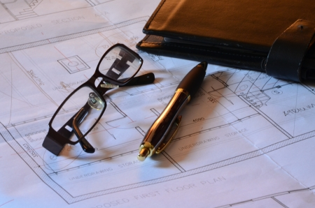 redemption of the world: Architects blueprints, glasses and pen