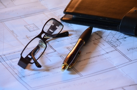 Architects blueprints, glasses and pen photo