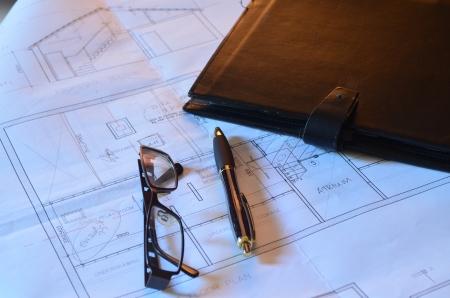 Architects blueprints, glasses and pen photo