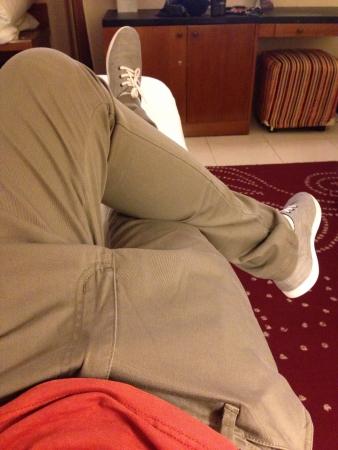 pants: legs crossed on bed Stock Photo