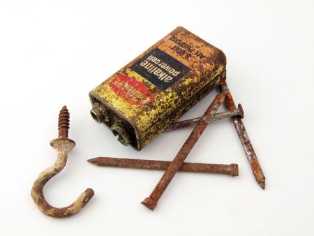 Rusty battery with nails and a hook.