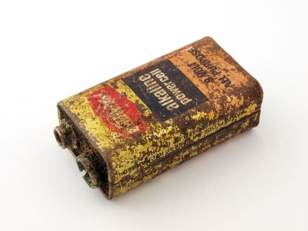 Old, flat rusty battery ready for safe disposal.