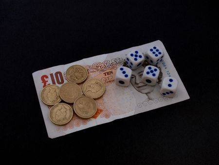 Concept of gambling showing coins, notes and  dice.