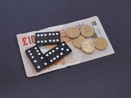 Concept of gambling showing coins, notes and dominos.