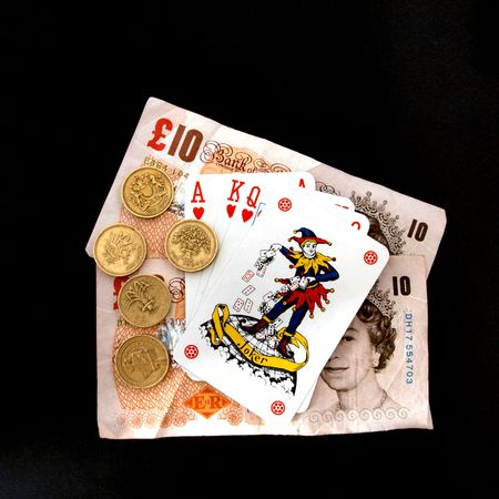 Concept of gambling showing coins, the joker  playing cards.