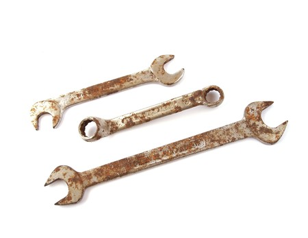 Rusty spanner on a plane white background.