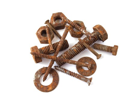 Rusty nuts, bolts and screws on a plane white background.