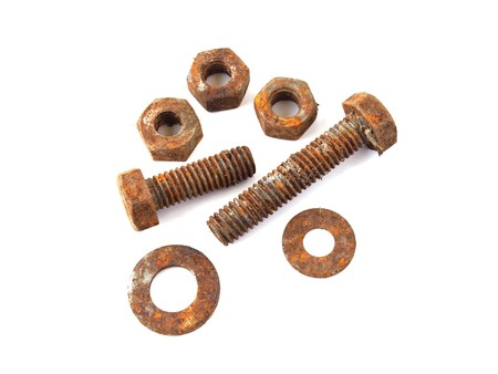Rusty nuts and bolts on a plane white background.