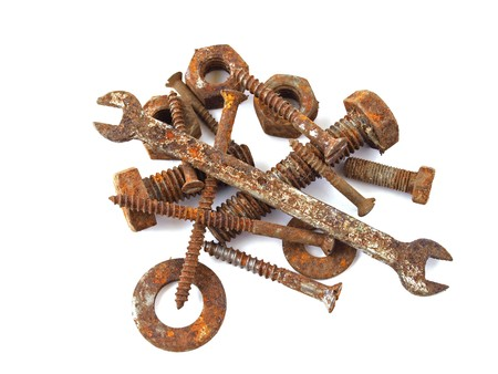 Rusty nuts, bolts, screws  and spanner on a plane white background.