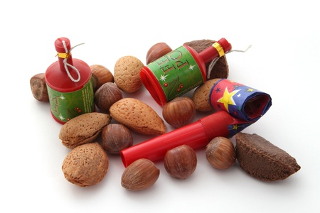 blowers: Mixed nuts with party blowers and poppers on a plain white background.
