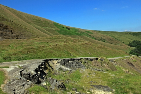 land slide: Mam Tor is a huge moving mountain slowly sliding into the Hope valley near Castleton in Derbyshire. It is still sliding today as can bee seen by what is left of the old road that was passable until as major slip in 1979.