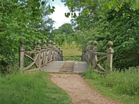 The Chinese bridge at the crossing point of two lakes in the grounds of Wimpole Hall. They were first started in 1697 and gradually extended until 1767 to the size and shape they are today. Stock Photo