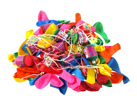 Close up of balloons and party poppers on a white background.