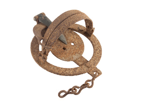 trickery: Close up photo of a rusty vermin trap on a white background.