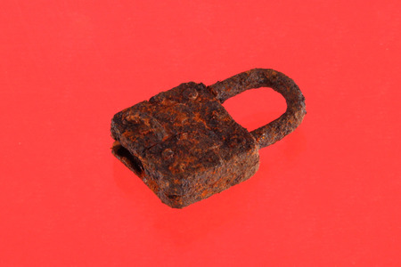 Rusty padlockon a red background